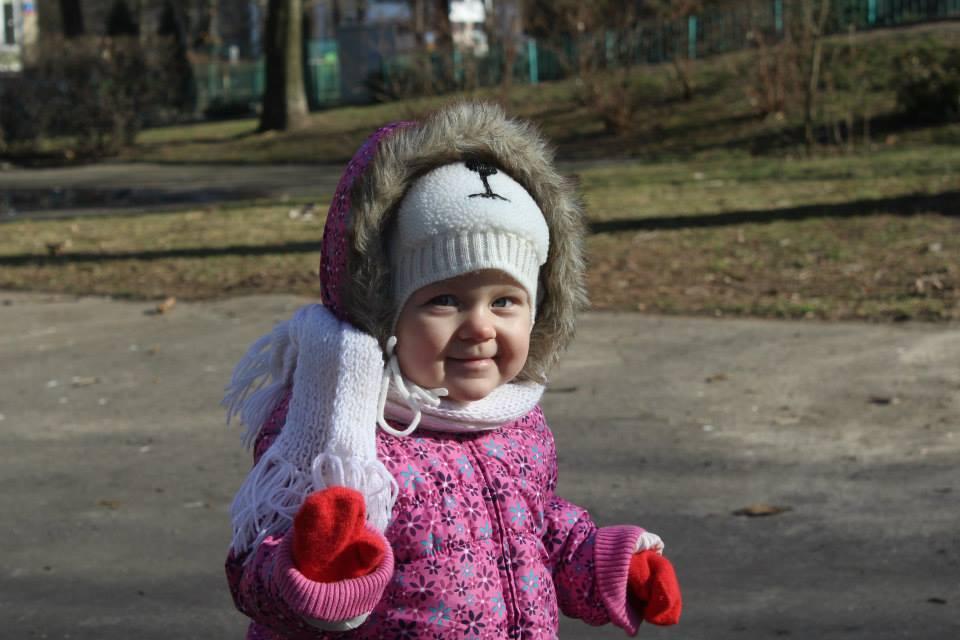 Dziewczyna w kurtce, czapce, wczesna wiosna, śmiejące się dziecko