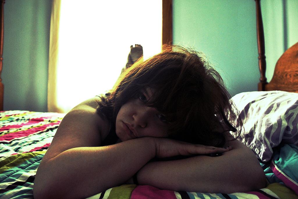 Czy Twoje dziecko doznaje przemocy rówieśniczej, dziewczyna leżąca na łóżku, smutny nastolatek